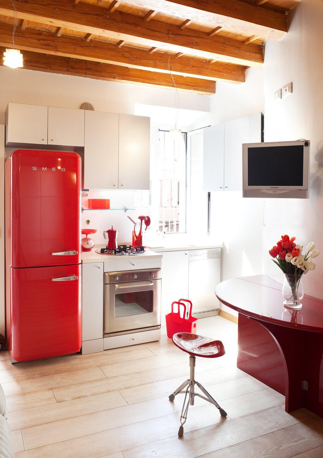 La cucina su misura, in laccato bianco opaco, prevede pensili di ...