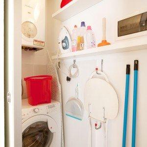 Lavanderia separata. La lunghezza della parete priva di aperture è stata sfruttata al centimetro per inserire l'armadio e anche per ricavare il vano chiuso dove sono installate la lavatrice e la caldaia: gli impianti sono condivisi con quelli del bagno adiacente.