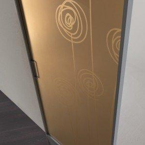 Plana Luxor, modello free della linea Bihome ha profilo d'argento e vetro reflex satinato bronzo, con sabbiatura Soffi.