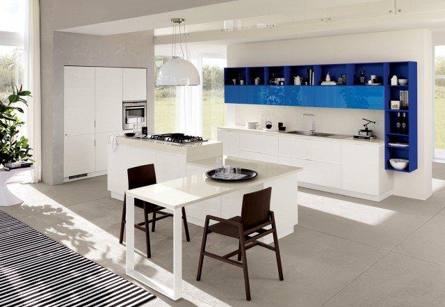 La cucina Mood di Scavolini (design by Silvano Barsacchi) presenta un'inedita isola con zona cottura e tavolo incorporato con piani a due altezze. I moduli a giorno sospesi creano un'interessante cornice per i pensili, ideali per ambienti open space. Le ante delle basi, delle colonne e dell'isola sono impiallacciate in rovere bianco assoluto (come la struttura); quelle dei pensili sono laccati lucidi azzurro riviera mentre gli elementi a giorno sono laccati opachi blu. I piani sono in quarzo bianco. La struttura è realizzata con panneli Idroleb del Gruppo Saviola – realizzati al 100% con materiale legnoso post-consumo certificato FSC e con le più basse emissioni di formaldeide. www.scavolini.it