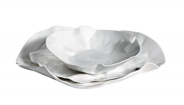 """Quando i piatti spiccano per originalità di design o per il colore particolare, meglio abbinare una tovaglia sobria, in tinta unita. Artigianali, i piatti in porcellana """"bone china"""" bianca, hanno la firma dell'artista; il set è composto da due piatti e una ciotola piccola, l'ingombro massimo è Ø 24 x H 5,5; prezzo da rivenditore. Adealaide di Driade  www.driade.com"""