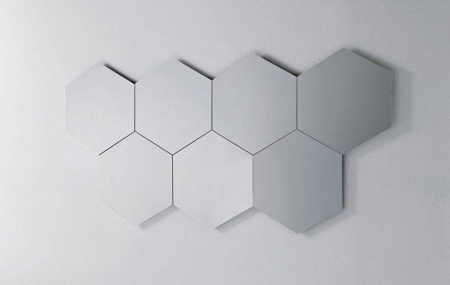 Una serie di elementi esagonali affiancati forma una grande composizione a parete. Possono essere dotati di impianto  di illuminazione perimetrale  ad accensione touch. Ogni singolo specchio misura L 80 x P 2,6 x H 70 cm e nella versione senza luce costa 183,70 euro Geometrika di Pianca www.pianca.com