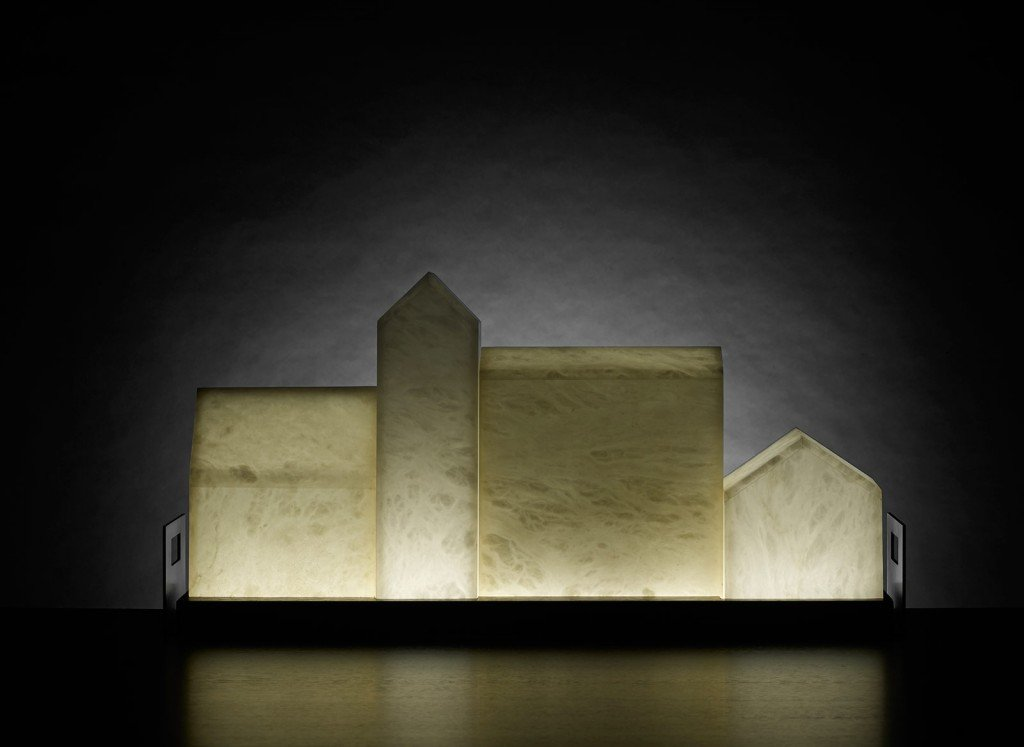 Piccole strutture architettoniche realizzate in alabastro bianco o sabbia formano Casetta di Promemoria, la lampada da tavolo che crea magiche suggestioni. La base è in rovere con maniglie in bronzo e l'illuminazione a led.  Misura L 67 x P 14 x H 32 cm. www.promemoria.com