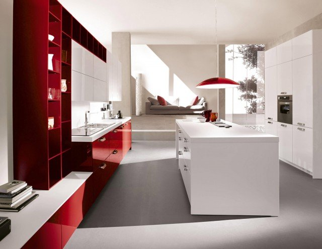 """. Un'isola candida in contrasto con i mobili-contenitore a giorno laccati rosso Ginger per Code Colour di Snaidero, la soluzione ideale per un ambiente giovane e grintoso. Gli elementi a giorno sono realizzati con moduli flessibili al centimetro, verticali o orizzontali, che hanno i ripiani interni regolabili e permettono di dare vita ad una parete attrezzata """"su misura"""". I piani di lavoro hanno uno spessore di 4 o 6 cm e sono disponibili in diversi materiali, dal laminato all'acciaio passando per il marmo e il granito; l'illuminazione è realizzata per mezzo di barre a Led alloggiate sotto il pensile. Una base chiusa da anta laccata lucido da 60 cm, prezzo 198 euro. www.snaidero.it"""