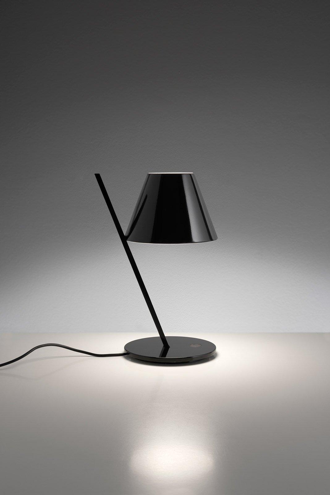Petite di Artemide è una lampada da tavolo realizzata in alluminio e plastica nera. Il design essenziale e rigoroso, un magico equilibrio tra pieni e vuoti, la rende facile da ambientare. Misura ø 16 x H 33 cm. www.artemide.com