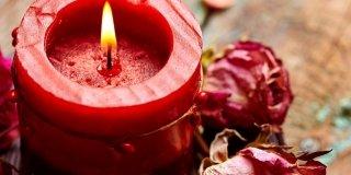 candela rossa con petali rosa essiccati
