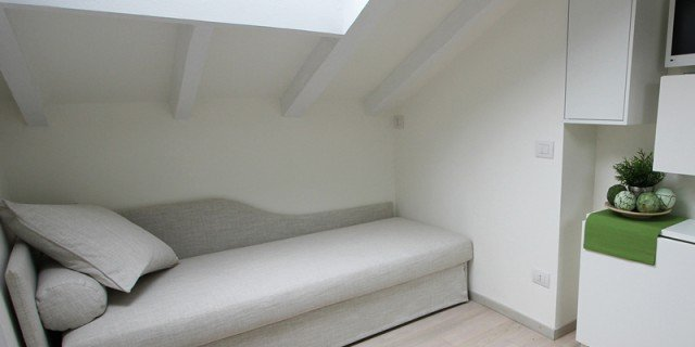 Per la mini mansarda: tanto bianco, superfici a specchio, mobili trasformabili