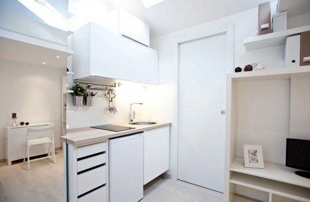 L'angolo cucina è ricavato nello stesso ambiente della zona giorno, protetto alla vista dalla profondità dell'armadio. Lo spazio disponibile è studiato al centimetro, per riuscire ad ospitare lavello, piano cottura a induzione, lavastoviglie, contenitore a cassetti e pensili, oltre a una serie di utili accessori a parete per riporre utensili o piccole stoviglie. Il candore della composizione è spezzato dal piano di lavoro di rovere chiaro, che ripropone l'effetto di calda luminosità dell'essenza del parquet di rovere sbiancato. Cucina sistema Metod di Ikea