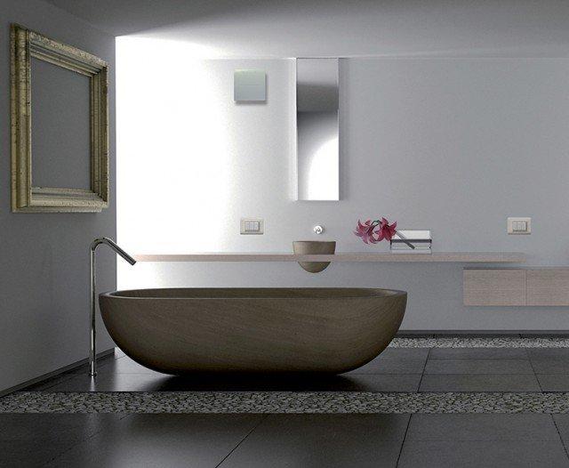 Minimalist white bathroom with stone bathtub and pebbles