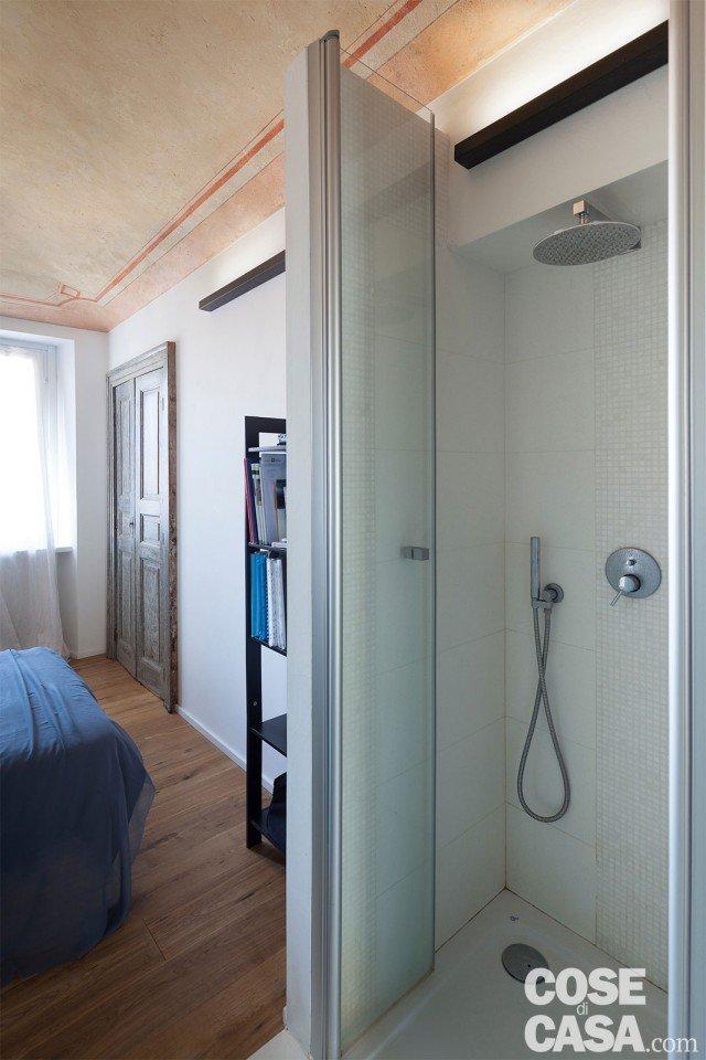 La doccia in muratura non arriva a tutta altezza per lasciare filtrare la luce naturale all'interno del box, rivestito in gres porcellanato e mosaico. Sulla parete di fronte al letto, una porta di recupero chiude un armadio a muro.