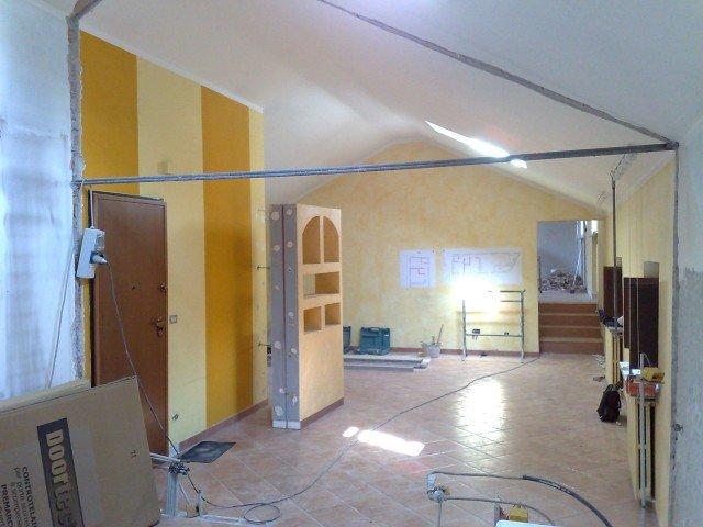 Dopo la demolizione del divisorio preesistente, il primo step è stato il fissaggio dei profili a parete e a soffitto conservando il tirante centrale  in acciaio che ha funzione portante.