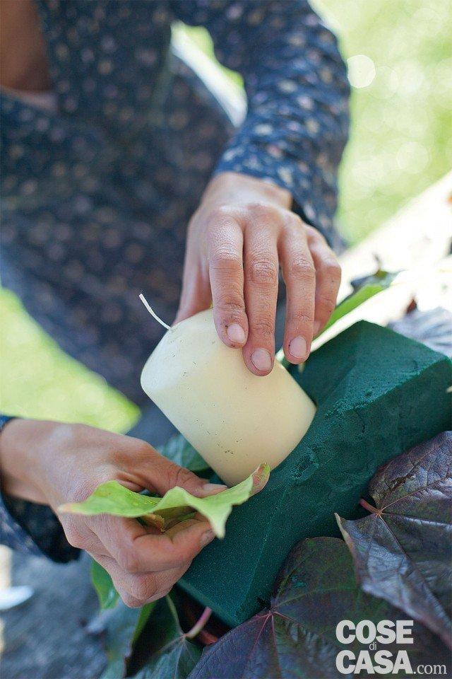 1. Posizionare la spugna nel sottovaso, eliminando la parte in eccesso e tagliando i 4 angoli in obliquo per aumentare la superficie utile a infilare i fiori. Mettere la candela al centro, facendola entrare nella spugna per circa 2-3 cm. Inserire il picciolo delle foglie più grosse tutto intorno alla base della spugna e poi fare un secondo giro nella parte alta, attorno alla candela, con le foglie più piccole. Mantenete una forma circolare attorno alla candela.