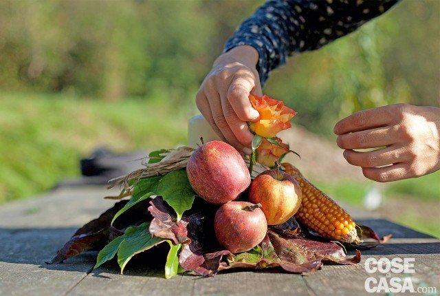 3. Tra le mele e le pannocchie sistemiamo, sempre a triangolo, 3 roselline, il cui gambo verrà tagliato a circa 10 cm dalla corolla, eliminando le foglie delle rose. Sul lato opposto mettiamo la zucca, facendo attenzione di farla ben aderire alla spugna. A fianco infiliamo il mazzetto di peperoncini. Inseriamo le altre 3 roselline tagliate anch'esse a 10 cm e spogliate delle foglie, seguendo sempre la disposizione a triangolo.