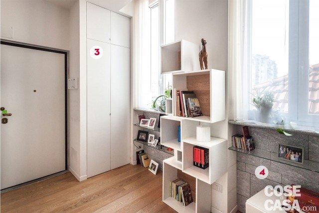 L'ingresso dell'abitazione è concepito come parte integrante del living, al quale è collegato tramite due passaggi aperti, a destra e a sinistra del pilastro centrale. La zona d'entrata è però anche uno spazio attrezzato, preziosissimo in una casa di piccole dimensioni come questa: ogni angolo libero è utilizzato per contenere, grazie a elementi d'arredo che – alternando pieni e vuoti – hanno un impatto visivo leggero e gradevole. La porzione di parete tra le due finestre all'ingresso è arredata con una composizione di cubi a giorno di diverse dimensioni e profondità, disposti in modo sfalsato: in laccato bianco opaco, hanno il fondo rivestito in rovere. Ai lati, i vetri sono schermati da tende leggere, in velo di organza semitrasparente.3. Il guardaroba incassato Entrando, a sinistra della porta, una spalla in muratura a tutta altezza disegna una rientranza profonda circa 60 cm dove è allocato l'armadio a muro per i cappotti, completo di uno scomparto indipendente nella fascia superiore. Le ante in laccato bianco opaco ne mimetizzano la presenza. 4. Nel sottofinestra L'altezza di circa 100 cm tra il piano del davanzale interno e quello del pavimento è stata utilizzata per inserire una serie di ripiani in cristallo. La profondità di circa 15 cm della rientranza è sottolineata dal rivestimento in beola della parete di fondo.