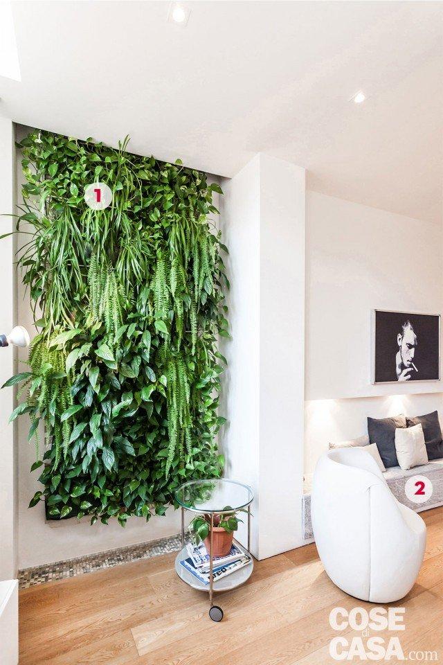 All'ingresso la parete verde è collocata nello spessore di una cornice in rilievo; in corrispondeza di quest'incavo, è stato realizzato a pavimento un inserto in mosaico, bianco e grigio, che spezza la continuità del parquet. Il tavolino rotondo su ruote con piano superiore in cristallo è di Ikea. 1. La parete verde La composizione, realizzata su disegno del progettista, è formata da felci, potos e spatifillum piantati in piccole tasche di feltro nascoste dalla vegetazione stessa. Il sistema di irrigazione dall'alto è automatico e temporizzato: l'acqua in eccesso finisce nello scarico presente sulla fascia a mosaico del pavimento.  2. Panca a doppia funzione Nel living la nicchia a parete permette di disporre della profondità di circa 40 cm, necessaria per inserire una panca bassa in muratura, rivestita in beola. Oltre a offrire sedute in più intorno al tavolo da pranzo, permette di alloggiare gli impianti di scarico di bagno e cucina.