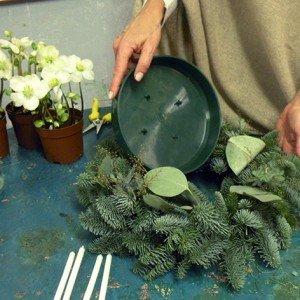 Alla base della ghirlanda, esattamente nel foro centrale, posizioniamo la vaschetta in plastica.