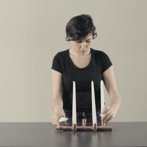 LUMIERE di Eleonora Musca: portacandele da tavolo dal design moderno e accattivante, realizzato utilizzando tubi in rame come base d'appoggio e mini doghe in legno per le candele.