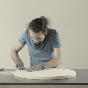 SESTO di Alberto Ghirardello: tavolino da caffè in legno di abete lamellare, minimal ed elegante: la base è composta da una tavola rotonda, listelli e tasselli in legno ed è sorretta da tubi di metallo.