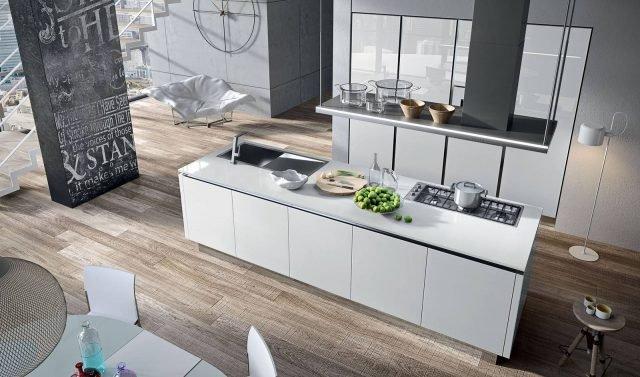 """Bijou di Aran è la cucina che si sviluppa su due linee parallele. L'isola è attrezzata con fuochi, una grande cappa sospesa e lavello in acciaio; l'armadiatura è formata da colonne con le ante sono in vetro bianco lucido che creano giochi di luce. Il top è in Okite bianco. Un modulo base da 60 cm, prezzo 281 euro. www.aran.it/""""ww.aran.it"""