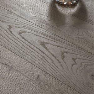 In tavolato sabbiato nella finitura grigio sabbia, il parquet Quercia Contorta Coll. Listoni Epoca di Cadorin è disponibile con spessore 14/16/21 mm, larghezza 140/170/195/220/230 mm e lunghezza fino a 2.900 mm (anche oltre per progetti speciali).