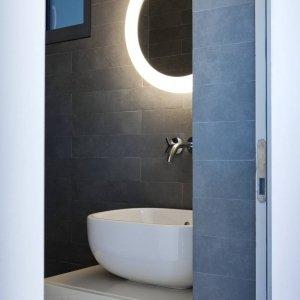 Bagno con rivestimenti in gres porcellanato e lampada a specchio di Pollice illuminazione.