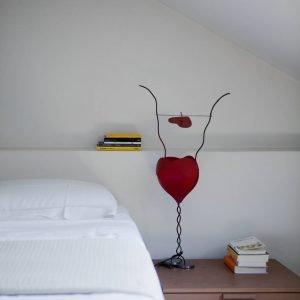 Di fianco al letto, sul comodino, la lampada  One From the Heart di Ingo Maurer.