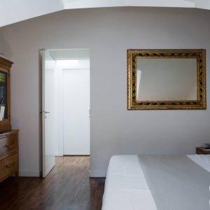 La camera è collegata direttamente all'ampia cabina armadio, nella quale troviamo moduli salvaspazio sotto lo spiovente. Cornice di famiglia.