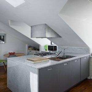 La cucina si concentra in un blocco a penisola con doppia profondità e basi sui due lati. Ospita le funzioni cottura e lavaggio. La cappa aspirante è fissata allo spiovente.