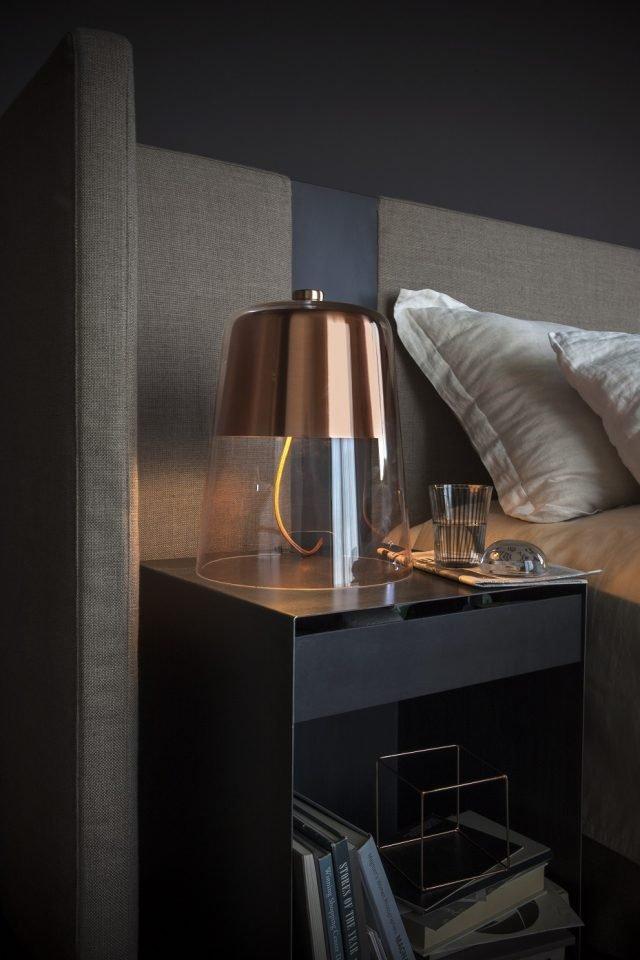 Semplice di Oluce prende il nome dall'essenzialità formale: via base e sostegni, per far appoggiare direttamente sul tavolo la struttura portante di vetro soffiato trasparente. La calotta metallica con finitura rame, tornita e lavorata in galvanica, satinata esternamente e verniciata bianco internamente, nasconde la fonte luminosa e porta anche il dimmer regolato dalla manopola sulla sommità del vetro. Ø 30 cm, H 36,5 cm. Prezzo 993 euro. www.oluce.com