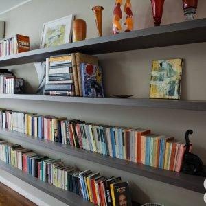 Libreria in legno naturale verniciato all'acqua, realizzata su disegno dell'architetto. Vasi di Venini.