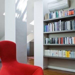 Lounge chair Bertoia Bird rossa di Knoll; libreria su misura con mensole in massello, ancorate direttamente al muro.