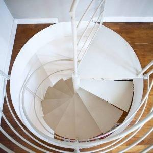 Al piccolo studio che dà accesso al terrazzo si giunge tramite una scala a chiocciola in metallo verniciato bianco, finitura che dà luminosità all'intero vano scala.