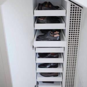 Nella cabina armadio, alcuni moduli sottotetto, progettati dall'architetto e realizzati da falegname, sono attrezzati come scarpiere con vassoi estraibili in lamiera forata.