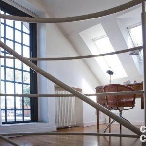 L'accesso al terrazzo avviene attraverso un piccolo studio arredato con scrittoio antico. Due finestre per tetti Velux forniscono grande luminosità all'ambiente. Sedia girevole di Alias, lampada Tolomeo di Artemide.