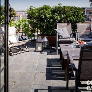 Terrazzo arredato con arredi Etnics, acquistati da Ecliss a Milano. Numerose piante in vaso poggiano su pavimento in pietra naturale.