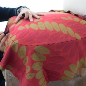 Per rivestire il piano di seduta, stendervi sopra una parte del tessuto e con il pennarello tratteggiare il profilo esterno. (Procedere allo stesso modo anche per il retro dello schienale).
