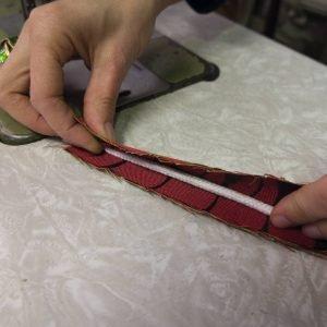 Chiudere all'interno della striscia un pezzo di corda bianca (della stessa  lunghezza), e cucire sul dritto del tessuto a formare un cordoncino, detto coda di topo.