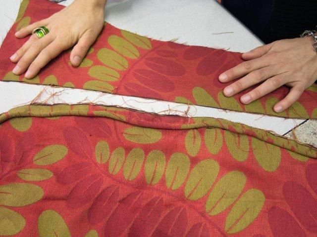 Cucire il cordoncino sulla stoffa precedentemente tagliata; quindi giuntare a questi una fascia alta quanto l'altezza della seduta, più 3/4 cm da ripiegare poi sotto la base. Cucire i due pezzi dal rovescio.