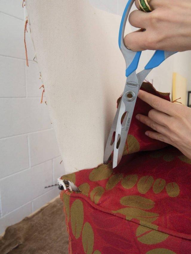 Per fare aderire bene il rivestimento ai contorni della poltrona, in corrispondenza dello schienale, fare due piccoli tagli nella stoffa alle due estremità.