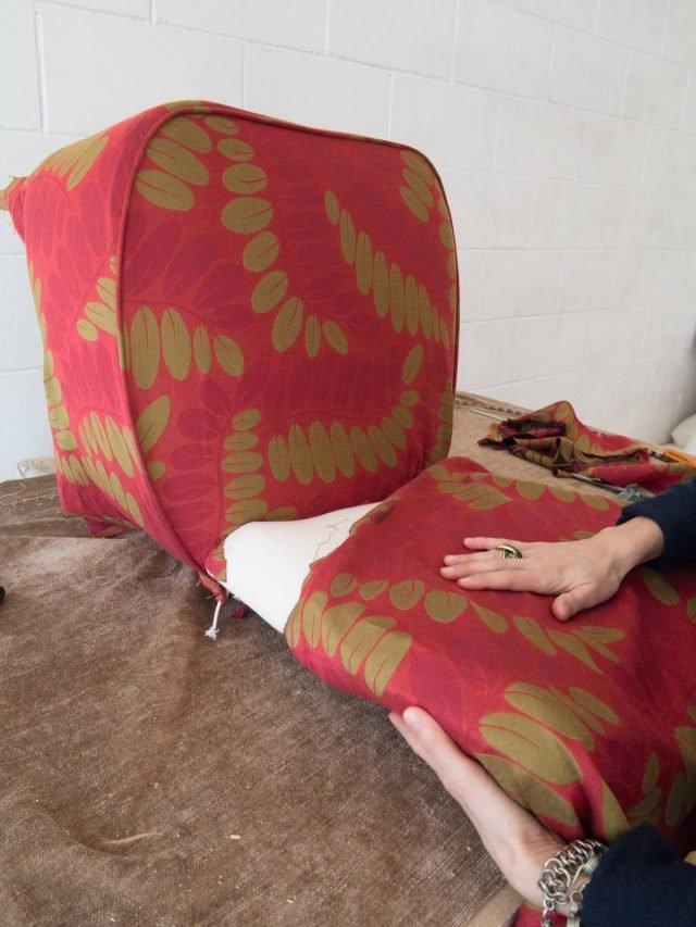 Appoggiare allo schienale un pezzo di stoffa, ripiegarlo sul retro, fare due tagli verticali lungo il bordo inferiore e inserire la stoffa in eccesso tra la seduta e lo schienale.