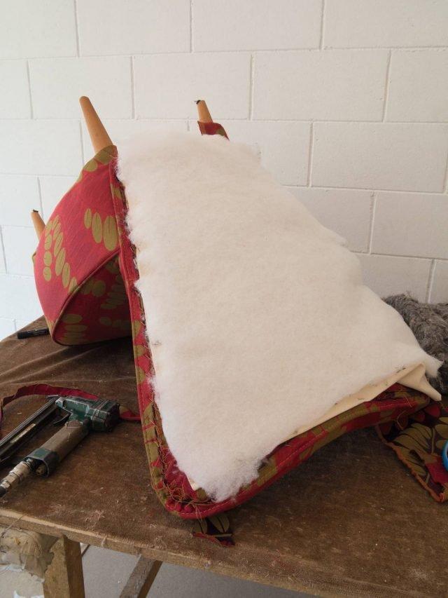 Dopo aver ribaltato la poltrona imbottire la parte posteriore con uno strato di 'filtro per cappe'. Con i punti attaccare il tessuto alla struttura.