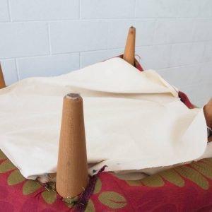 Infine, ribaltare la poltrona e coprire il fondo con una tela di cotone bianco grande abbastanza per nascondere le cuciture del tessuto di rivestimento. Fissarlo con i punti, ripiegando il bordo perché non si sfilacci.