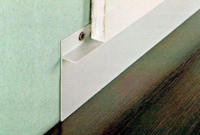 """Esempio di applicazione del nuovo battiscopa Proskirting Ins di Progress Profiles. In alluminio anodizzato argento, è composto da una parte verticale, munita di fori all'estremità superiore, da fissare con tasselli, e da una parte orizzontale sporgente, sulla quale appoggiare il cartongesso. La cavità che si viene a creare può essere ricoperta con qualsiasi tipo di battiscopa (per esempio piastrelle o parquet) o finitura personalizzata. Può anche essere lasciata libera, in modo da creare l'effetto di una parete """"sospesa"""". www.progressprofiles.com"""