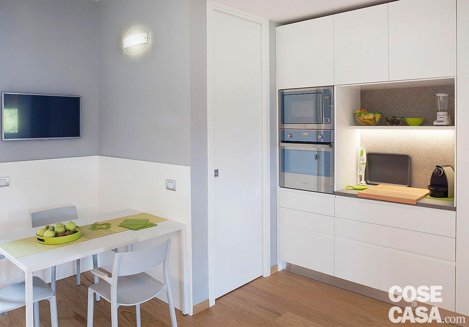 Cucina a vista sul soggiorno nel sottotetto con terrazzi a tasca