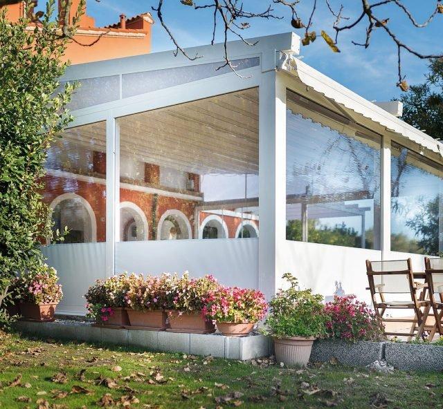 """La struttura Gennius A3 di KE Protezioni Solari (www.keoutdoordesign.it), in alluminio e con tenda a pacchetto in pvc, diventa veranda con l'aggiunta di vetrate scorrevoli e finestre """"Cristal""""."""
