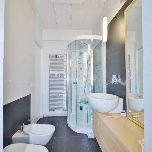 """Nel bagno del primo piano: doccia-sauna (Teuco """"Art. 157""""), sanitari sospesi IO di Flaminia, mobile in rovere sbiancato, termoarredo in acciaio Runtal. Piastrelle in gres lavagna (C.Fiandre) per pavimenti e rivestimenti,  completati da tinteggiatura a marmorino."""