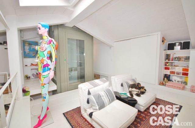 Livello sottotetto: poltrone letto Zip Butaca Canna di La Forme - Julia Group; zona relax con chaise longue di Cassina, tappeto persiano; manichino dell'artista Andy dotato di lettore MP3 e cassa.