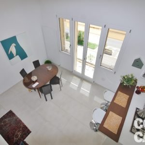 La zona pranzo vista dal livello superiore sottotetto. Gli infissi basso-emissivi del primo piano sono in legno e alluminio (interno-esterno), serie New Dual di Spi.