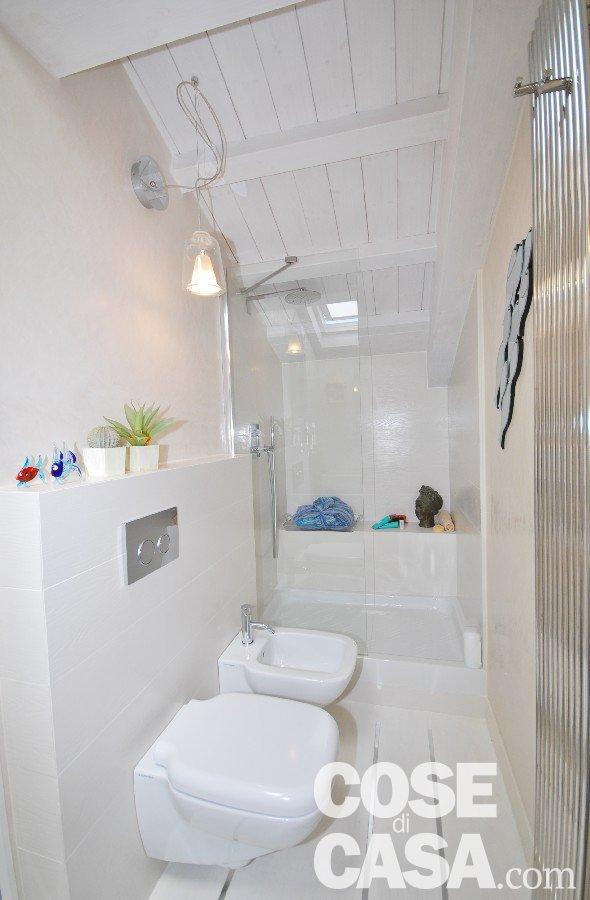 Sempre nel sottotetto, nel bagno doccia  con pannello in vetro temperato di Samo, piatto doccia in porcellana, termo arredo in acciaio di Cordivari. Finestre per tetti Velux.