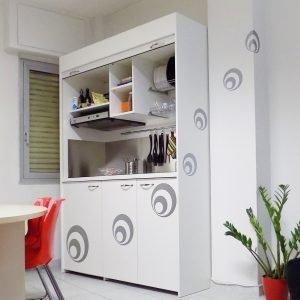 SI CHIUDE CON UNA SERRANDA: Cucina armadio Art. 125 compact di Nigth&Day/Vivilospazio. Design Vanna Migliaccio, multistrato laminato o laccata ha la serranda saliscendi che la nasconde dopo l''utilizzo. È dotata di stencil da posizionare come meglio si desidera, per un tocco decorativo. Misura L 154 x P 60 x H217. Dispone di cappa, 2 fuochi a induzione, mini frigorifero, lavello a una vasca, miscelatore con doccetta: prezzo tutto compreso 1.600 euro. www.vivolospazio.com